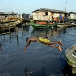 A boy jumps into the lagoon for a ball at the Makoko slum in Lagos, Nigeria. © Emmanuel Quaye / Twenty Ten Project / Africa Media Online