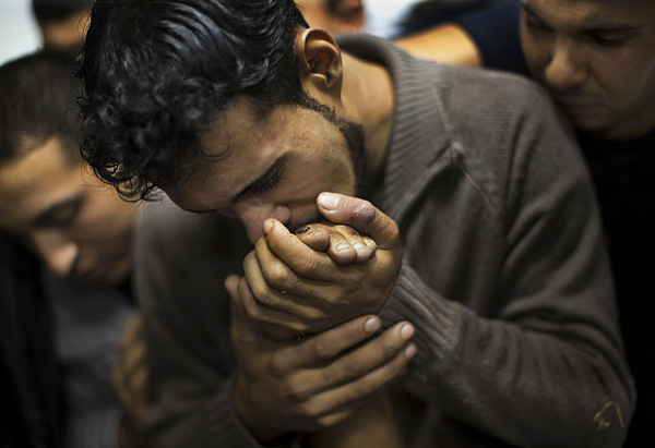The Winner of the 9th CHIPP Awards. A Palestinian man kisses the hand of a dead relative in the morgue of Shifa Hospital in Gaza City, Nov. 18, 2012. © Bernat Armangue/AP