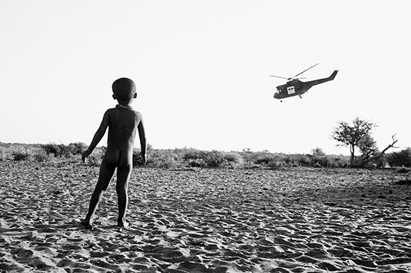 A young child watches on as a supply helicopter leaves